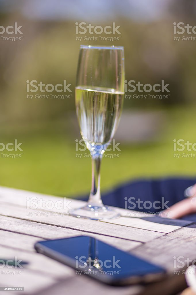 Glass of champagne and a smartphone stock photo