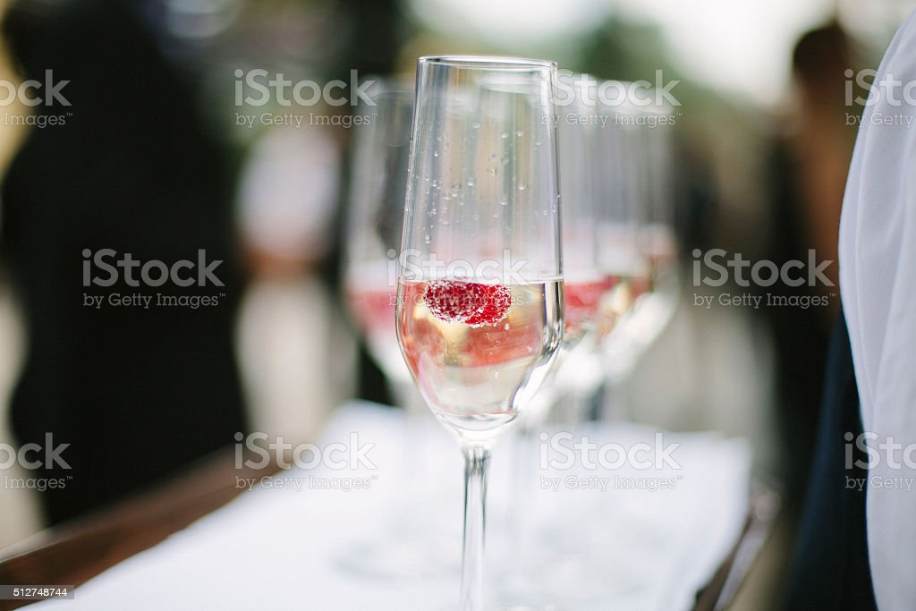 Glass of champagne with raspberry. stock photo