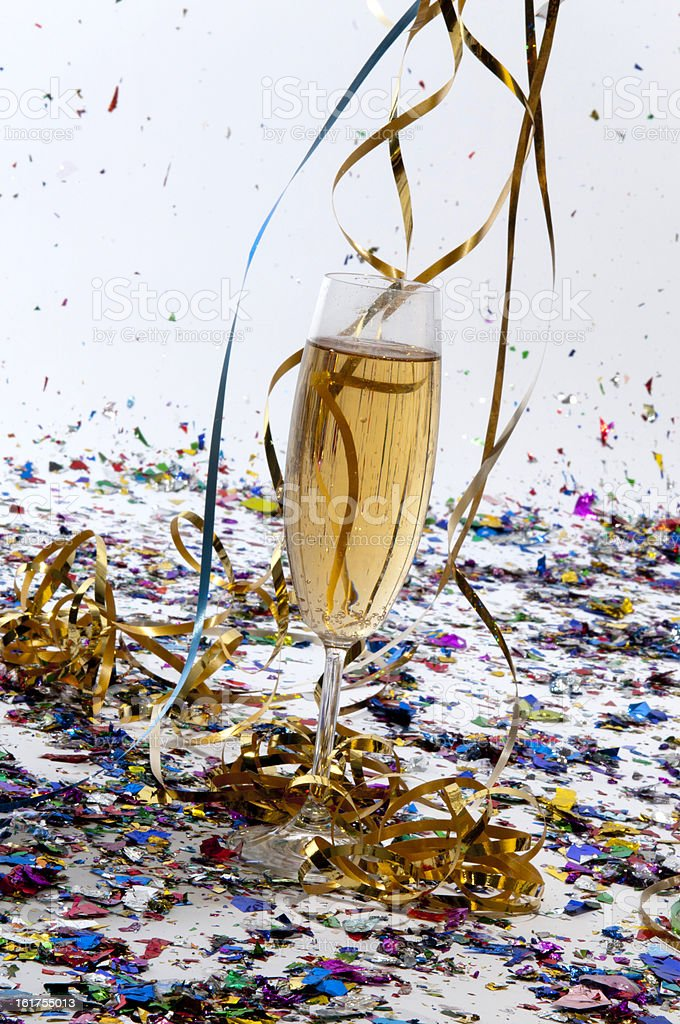 Glass of champagne with streamers and confetti royalty-free stock photo