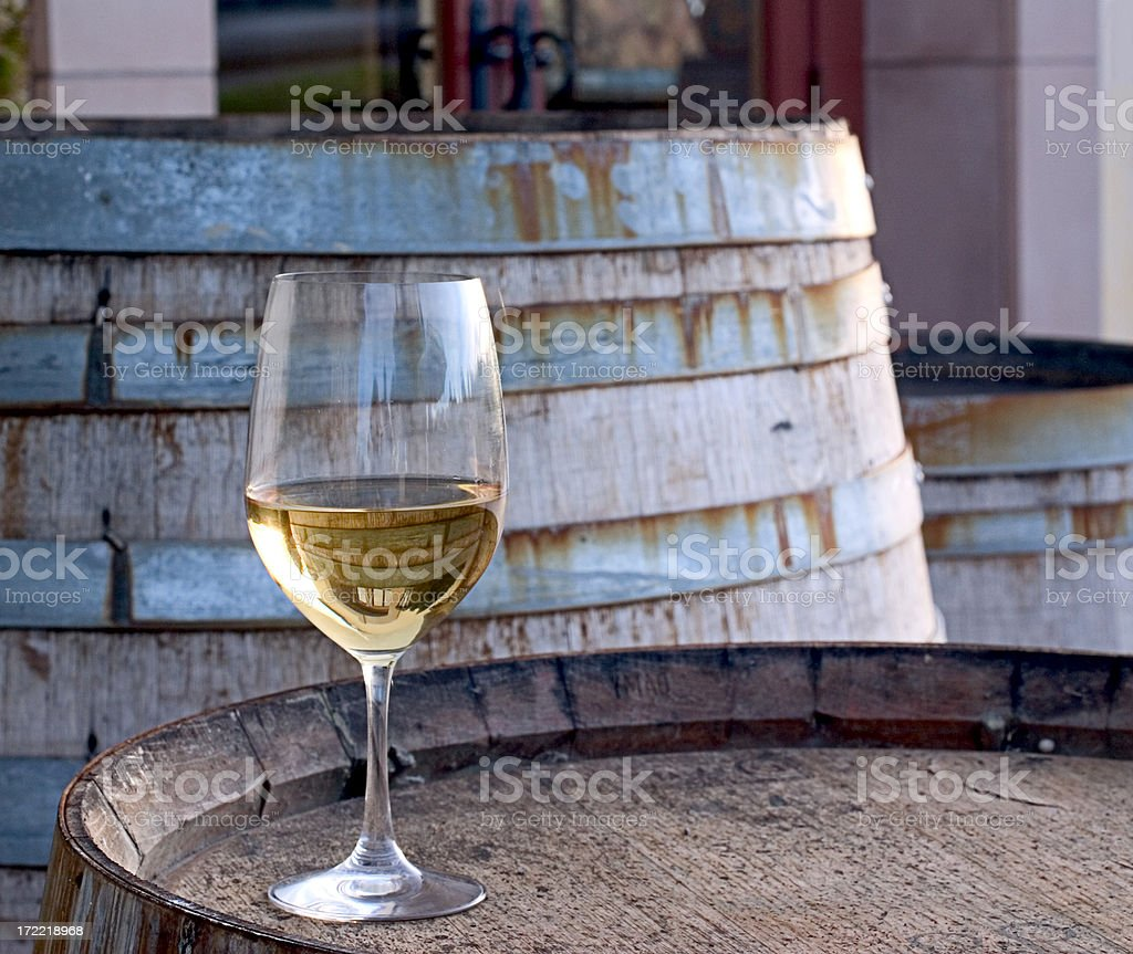 A glass of Chardonnay sitting on a barrel stock photo