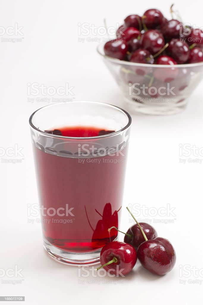 glass of cherry juice with cherries in background stock photo