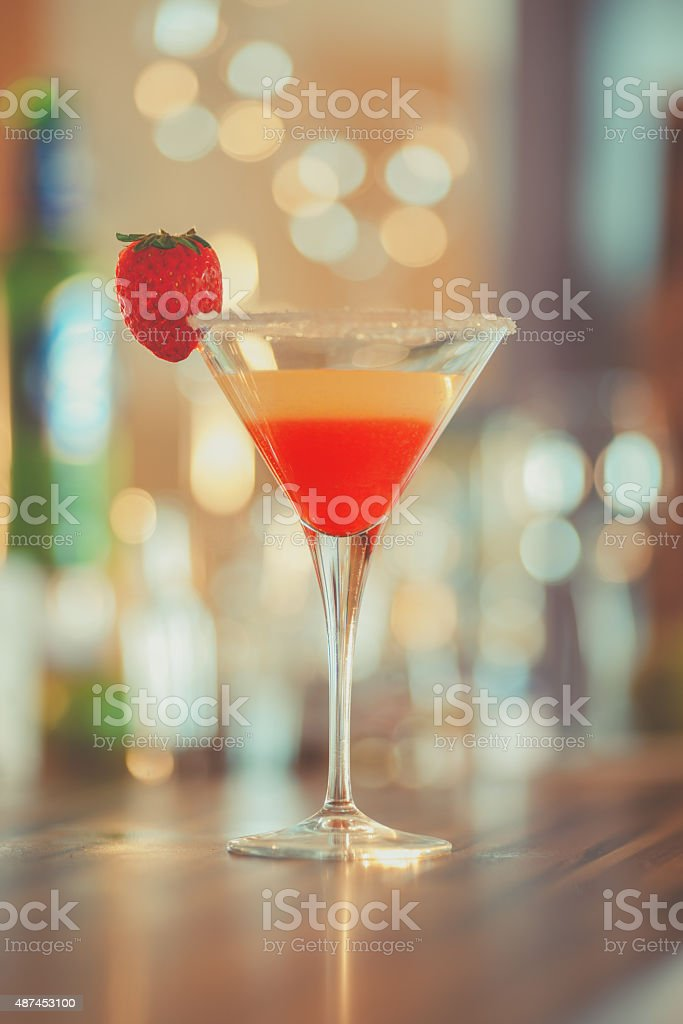 glass of cocktail garnished with strawberry stock photo