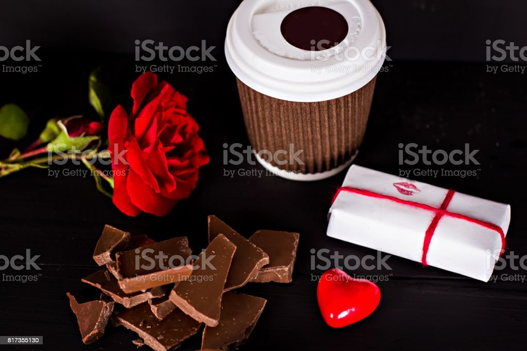 A glass of coffee, chocolate, a red rose, a gift. stock photo