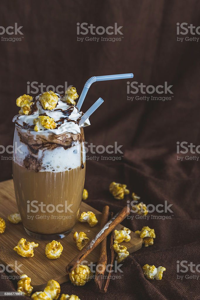 Glass of coffee with sour cream, caramel popcorn and chocolate stock photo