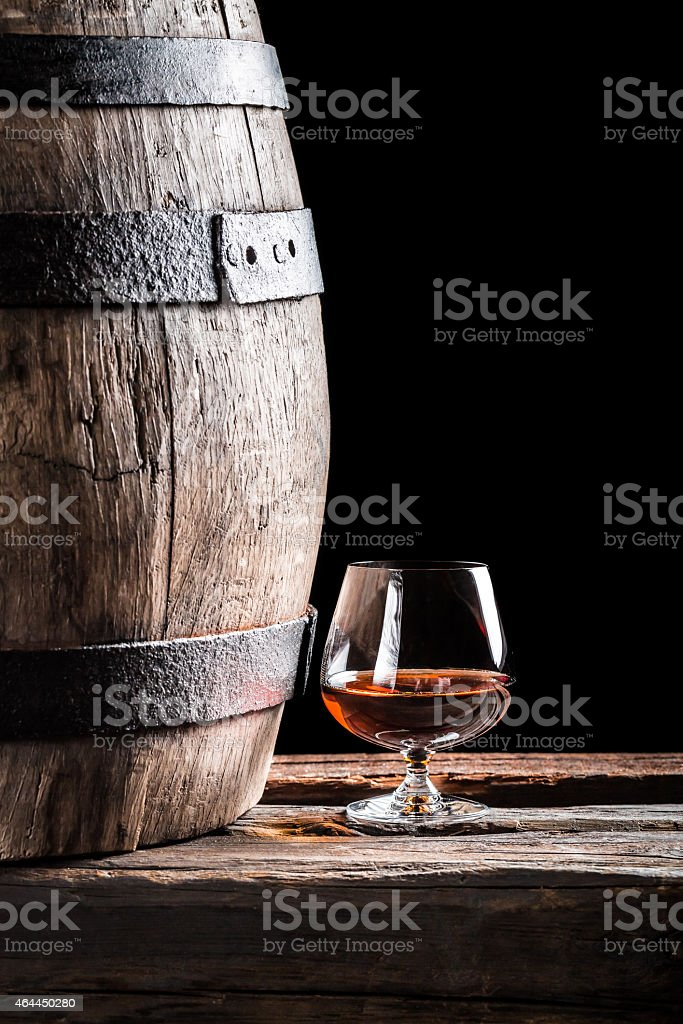 Glass of cognac and old oak barrel stock photo