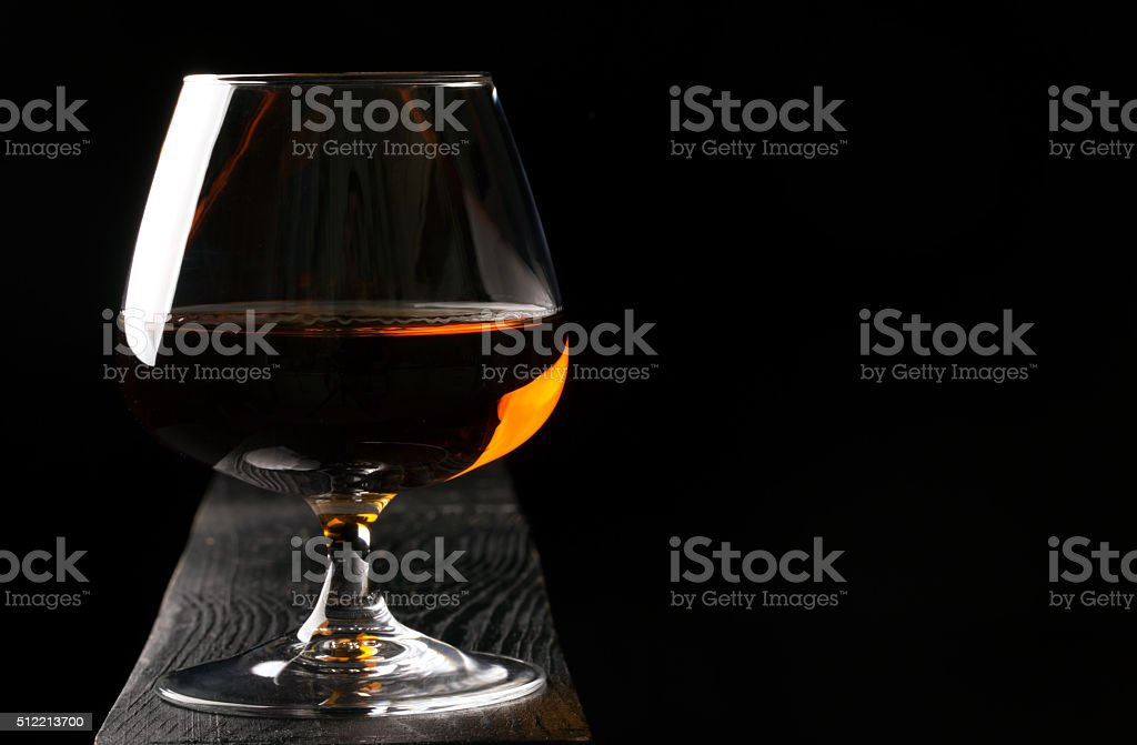 Glass of cognac on the black table stock photo