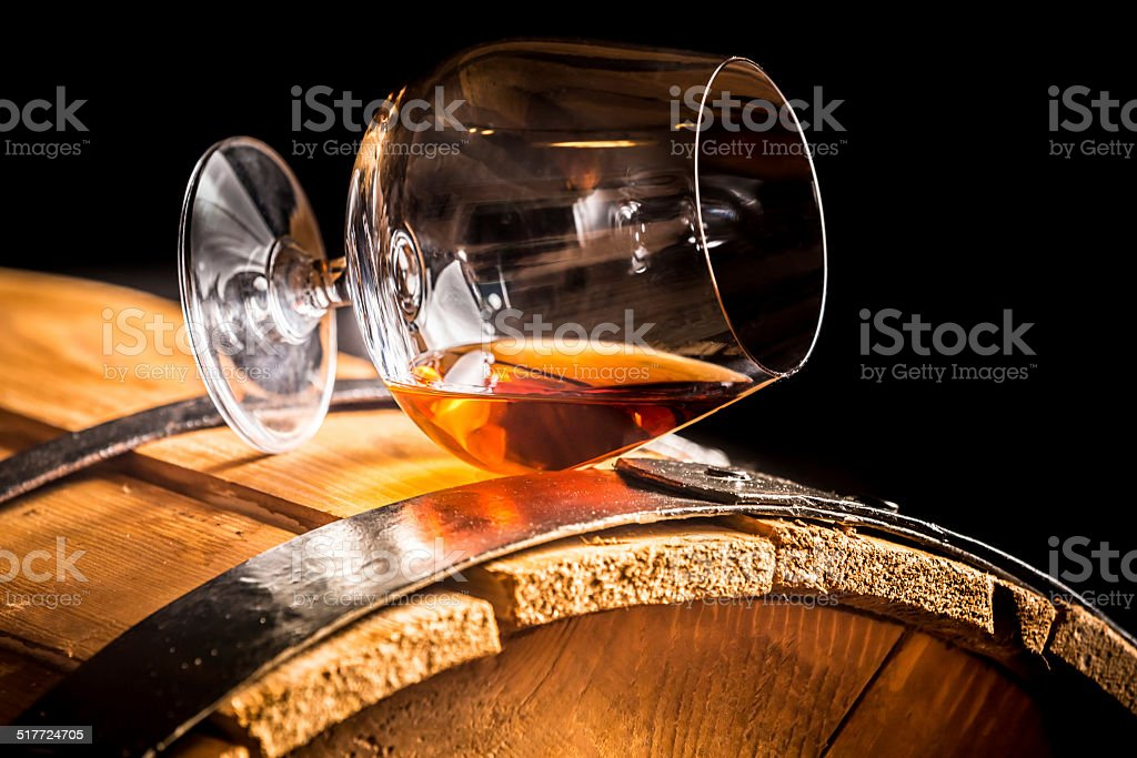 Glass of cognac on the old wooden barrel stock photo