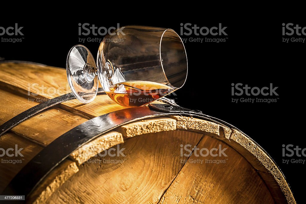 Glass of cognac on the vintage barrel stock photo