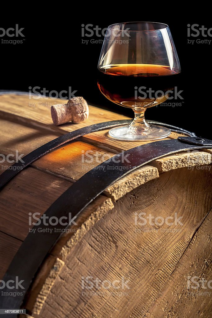 Glass of cognac on the vintage wooden barrel stock photo