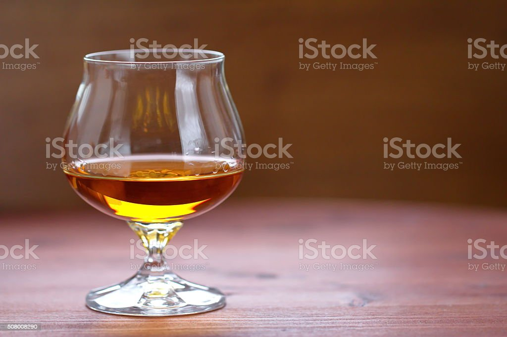 Glass of cognac on the wooden table stock photo