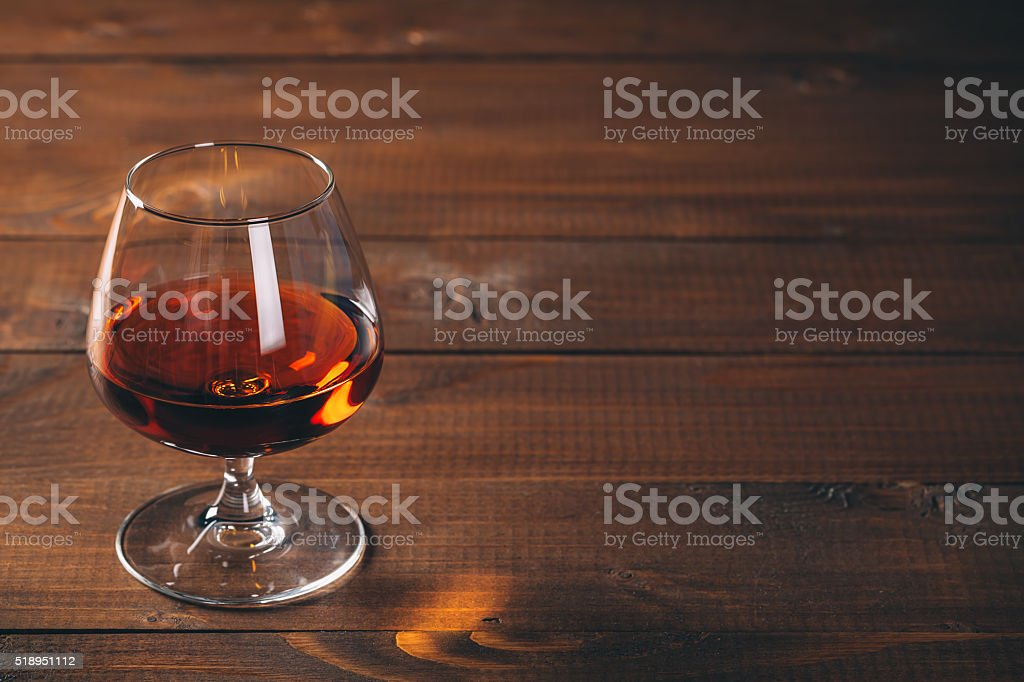 Glass of cognac on the wooden table. stock photo