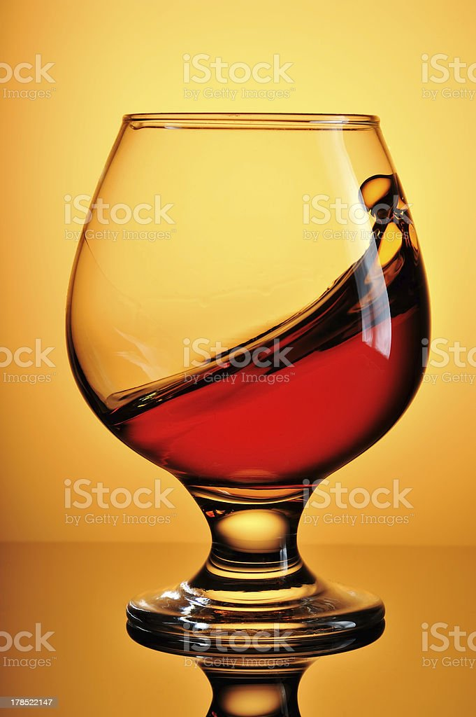 Glass of cognac on yellow background royalty-free stock photo