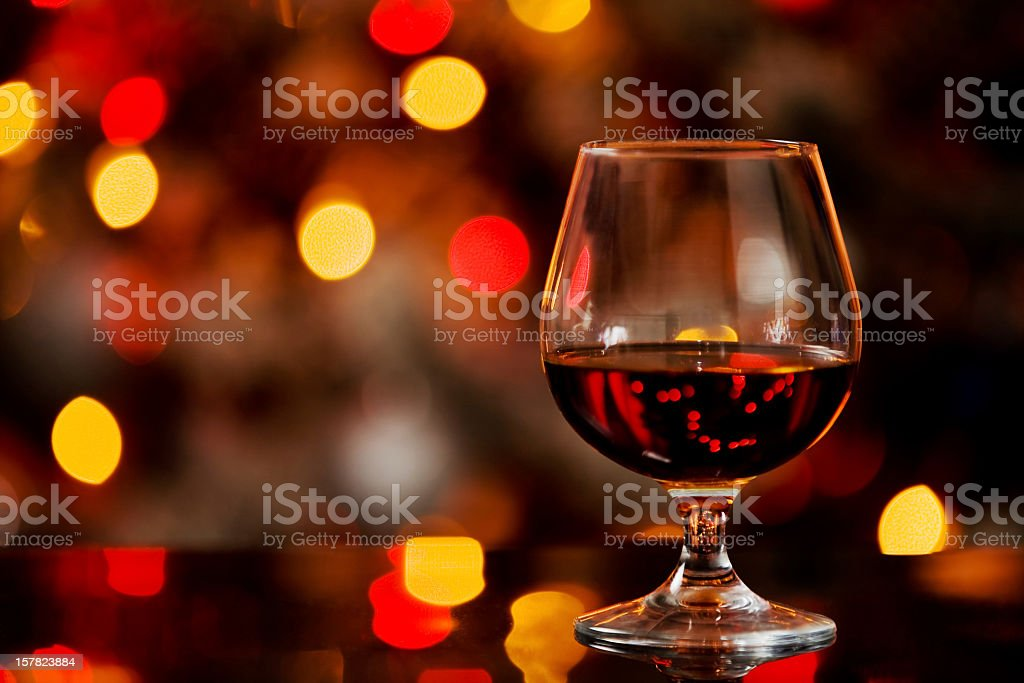 Glass of cognac with out of focus lights in background stock photo