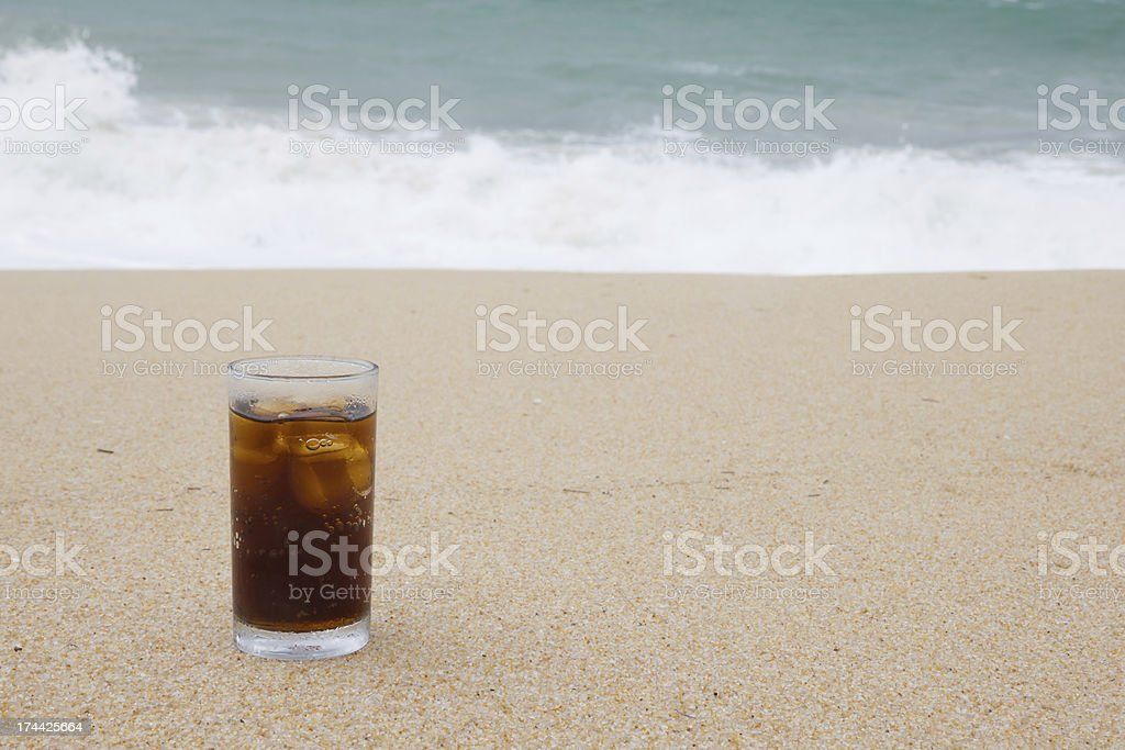 Glass of cola on the beach royalty-free stock photo