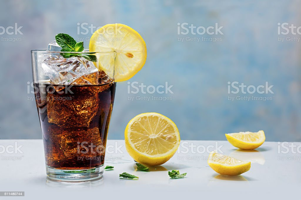 glass of cola  with ice cubes and lemon slices stock photo