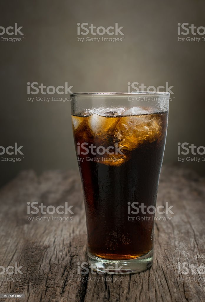 glass of cola with ice cubes on wood table. stock photo