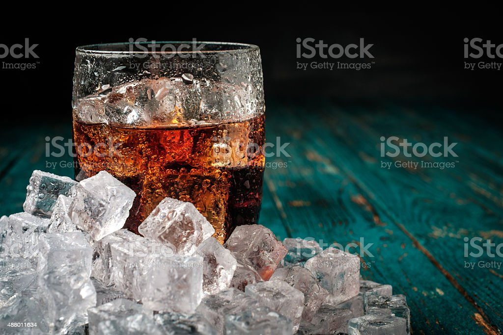 Glass of cola with ice on a wooden table. stock photo