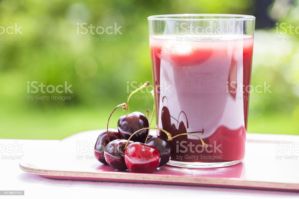 Glass of Cold cherry  juice in garden stock photo