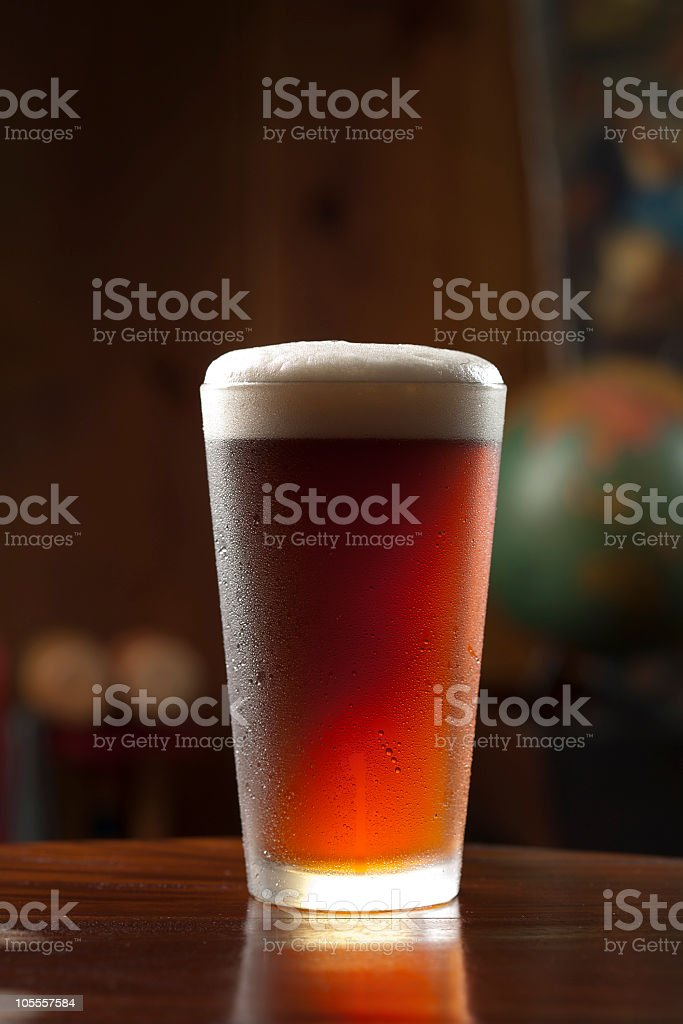 Glass of cold foamy beer on a bar royalty-free stock photo