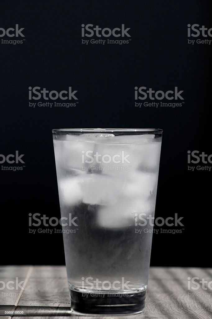 Glass of cold water with ice cubes on wooden table stock photo
