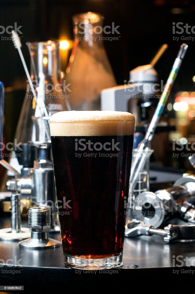 Glass of dark craft beer with brewing supplies stock photo