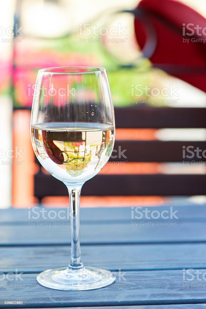 Glass of delicious fresh white wine on summer terrace. Outdoors. stock photo
