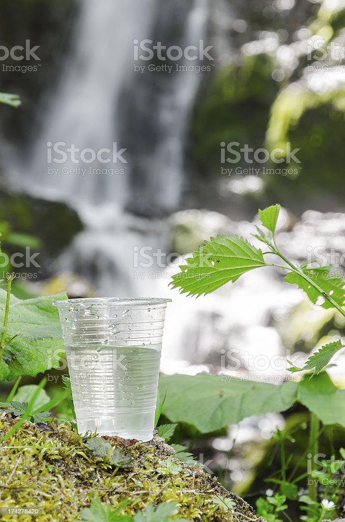 glass of drinking water near the foliage blurred waterfall stock photo