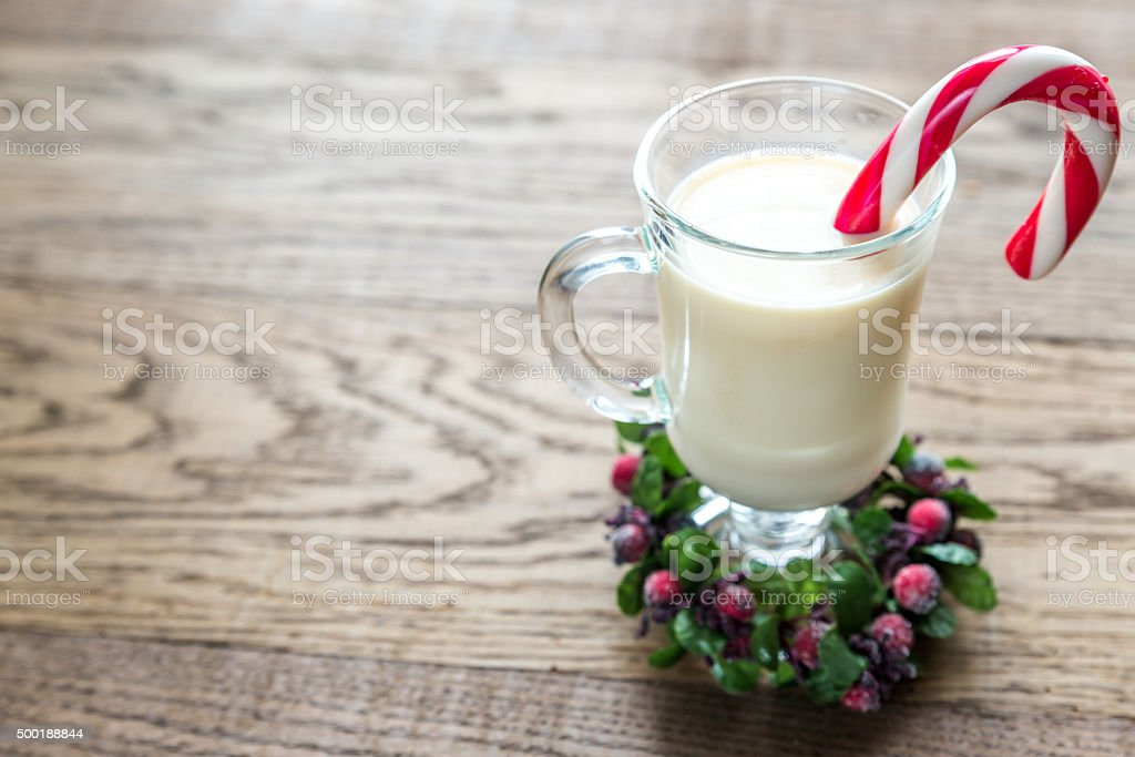 Glass of eggnog with candy cane stock photo