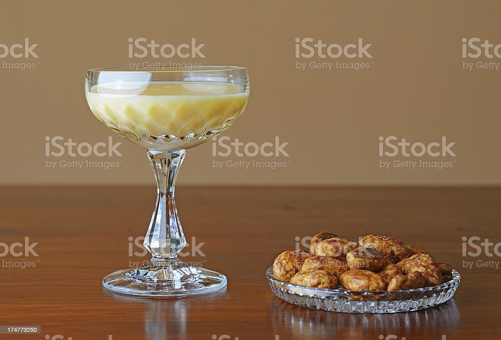 Glass of eggnog with roasted almonds on brown table stock photo