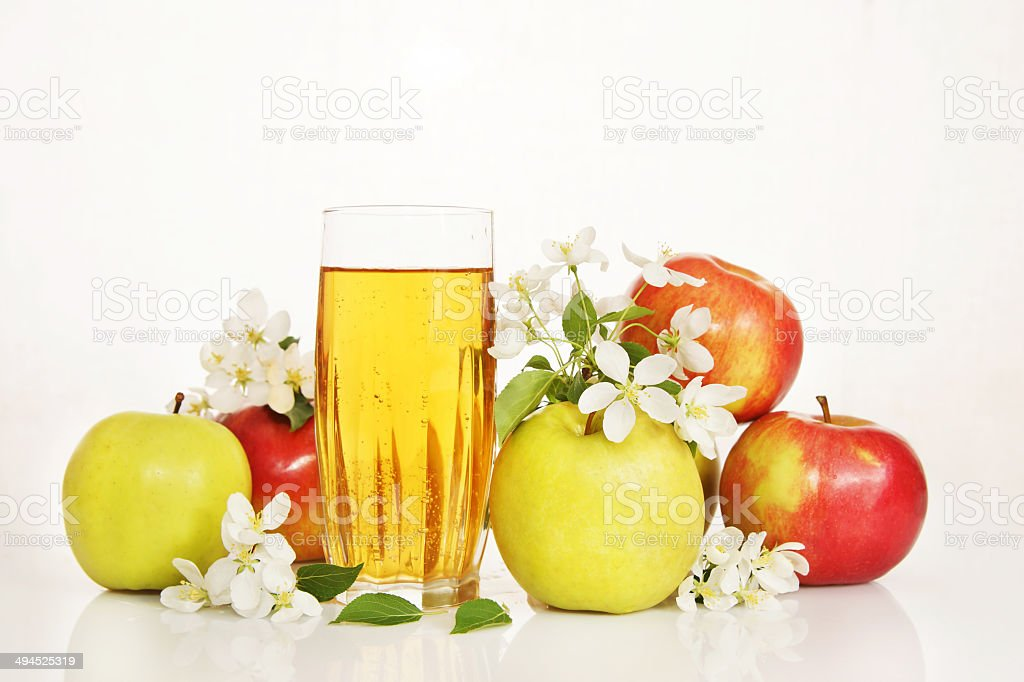 Glass of fresh apple juice with ripe apples and flowers stock photo