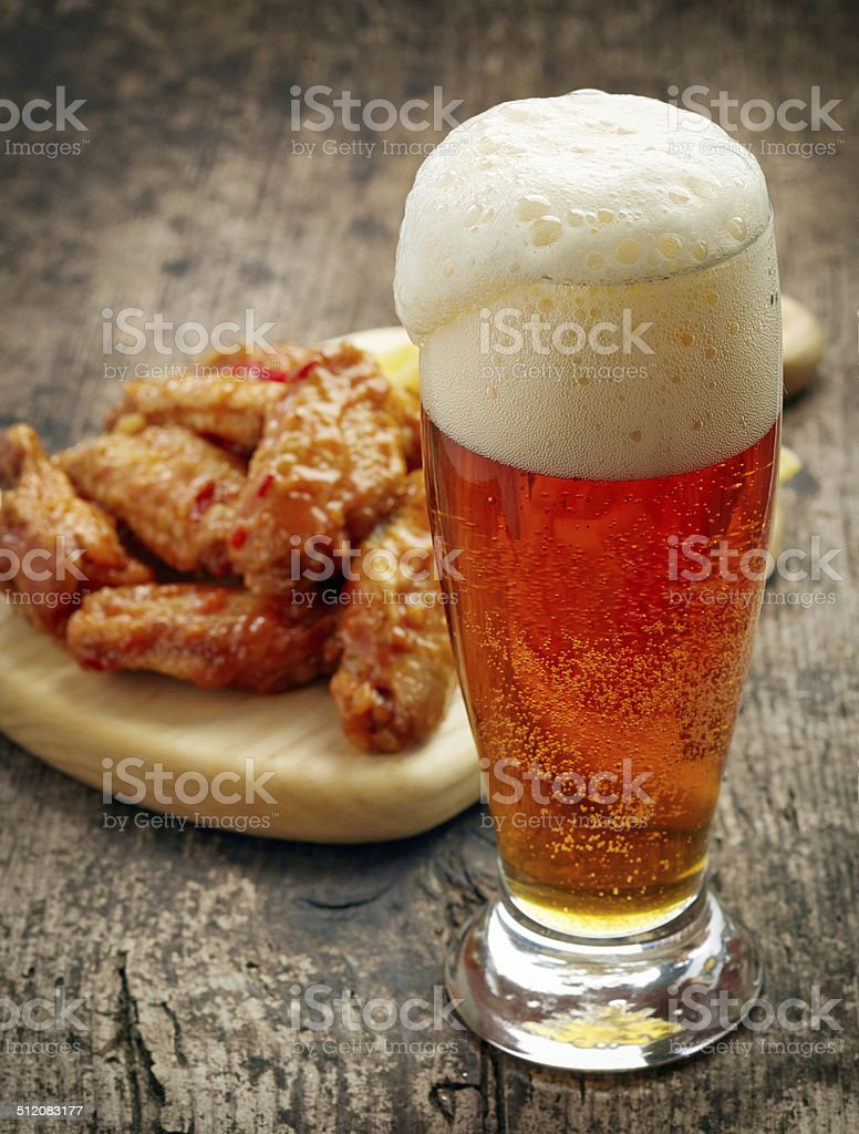 glass of fresh beer and fried chicken wings stock photo