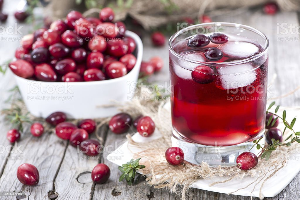 Glass of fresh cranberry juice and a bowl of cranberries stock photo