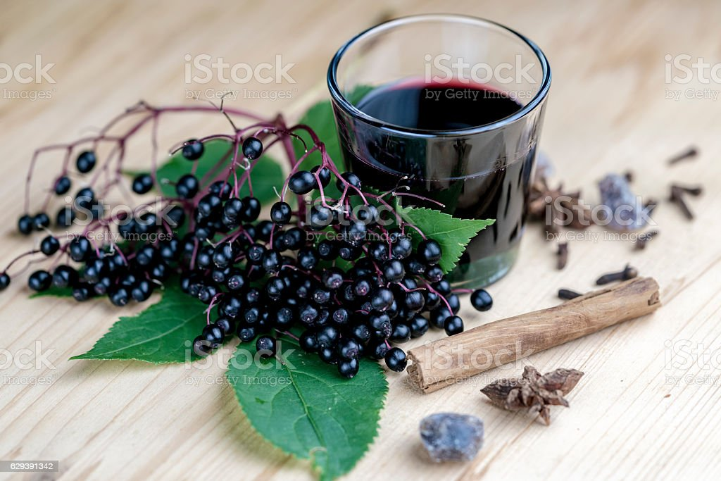 Glass of fresh elderberry syrup with ingredients stock photo