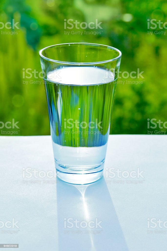 Glass of fresh water on green nature background royalty-free stock photo
