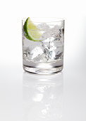 A glass of gin and tonic with ice and a slice of lime