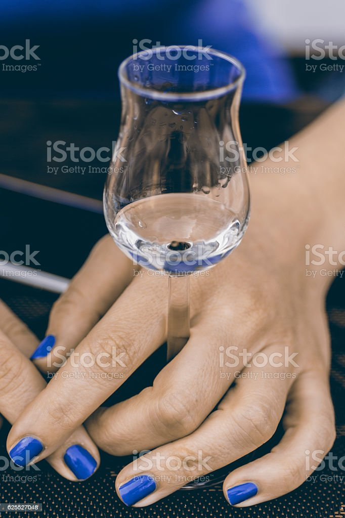 Glass of Grappa in Woman€™s Hands. Grape Brandy or Schnapps. stock photo