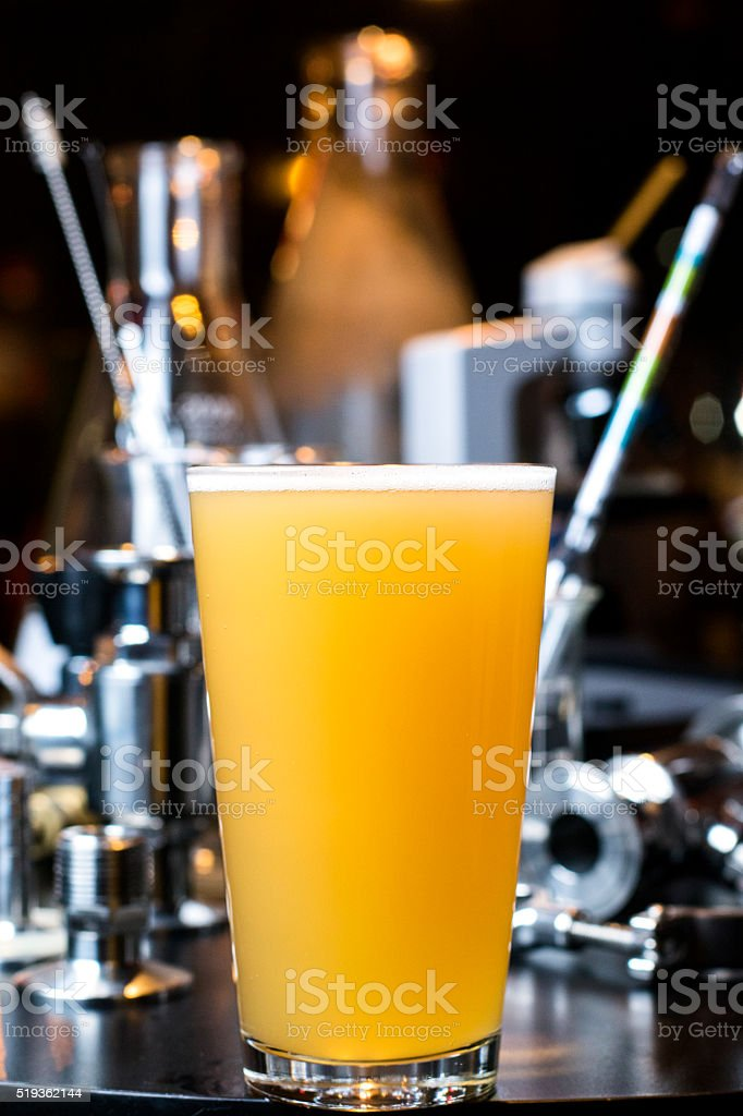 Glass of Hefeweizen with brewing supplies stock photo