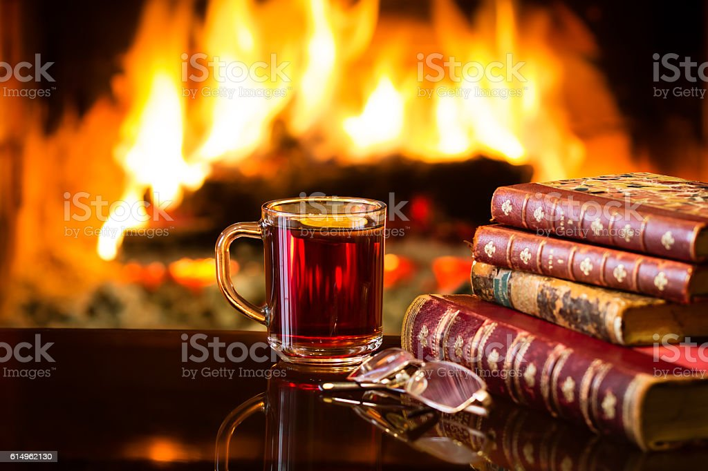 Glass of hot drink wine, antique books, fireplace stock photo