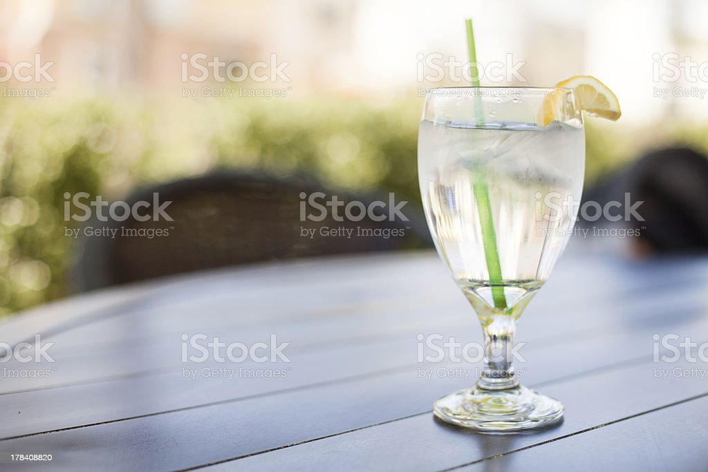 Glass of Iced Water with Lemon sits on Outside Table royalty-free stock photo
