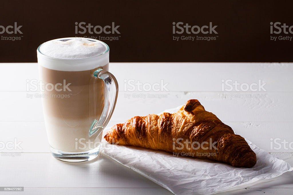 Glass of latte macchiato and French croissant. stock photo