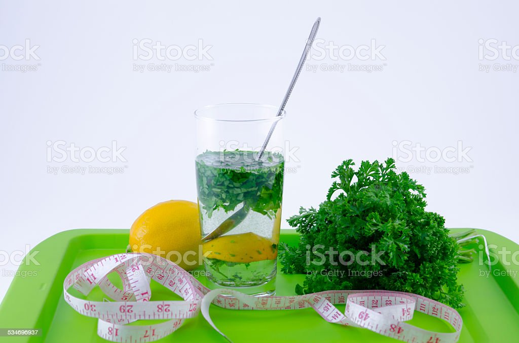 Glass of lemon and parsley on a green tray royalty-free stock photo