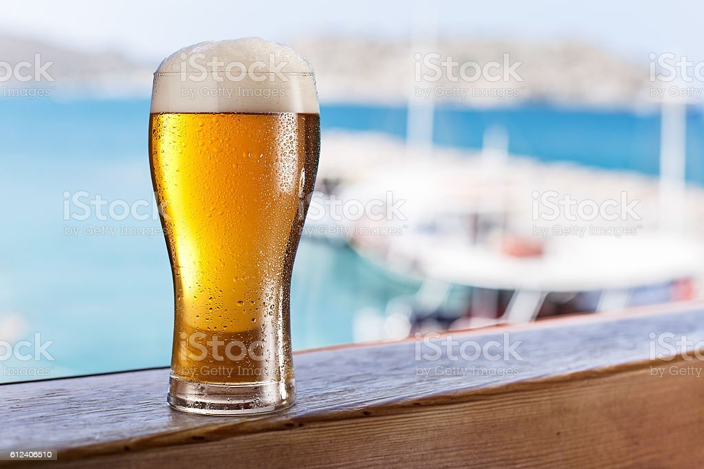 Glass of light beer on the  seaside bar counter. stock photo