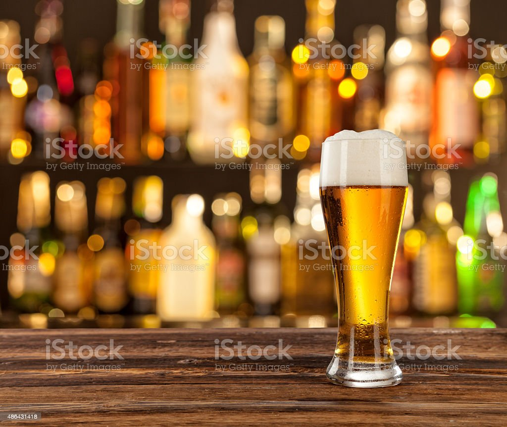 Glass of light beer with bar on background stock photo