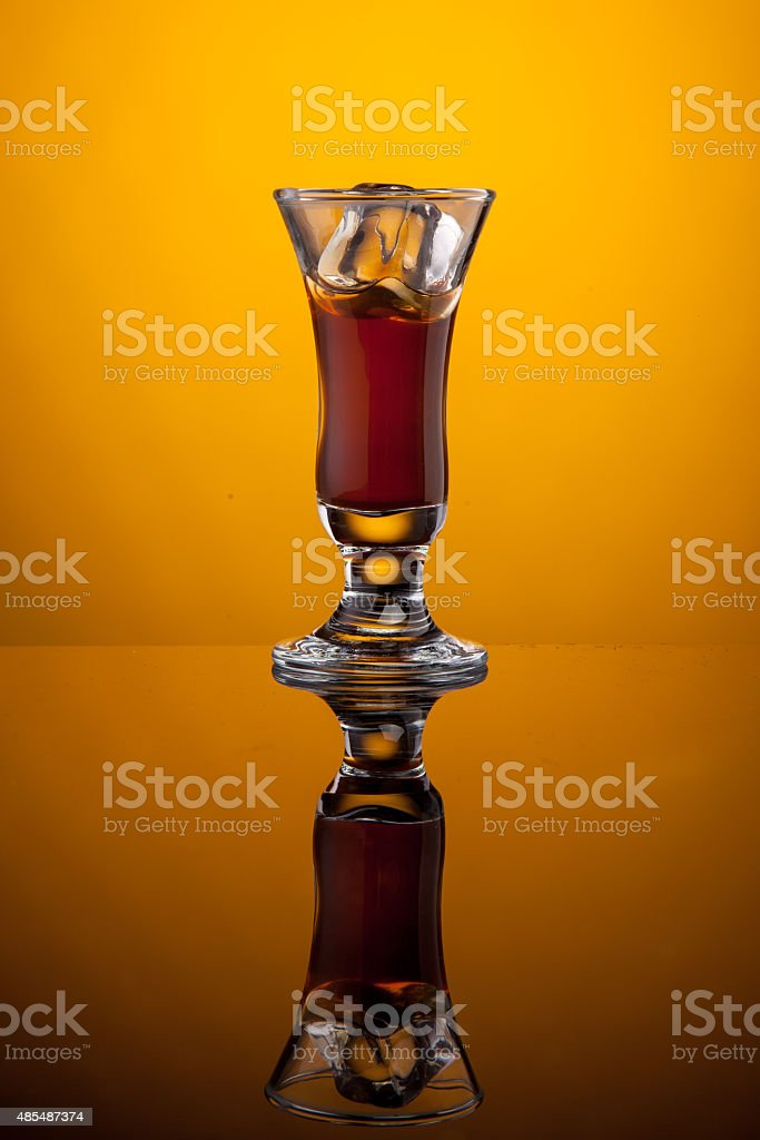 Glass of liqueur with cube ice stock photo