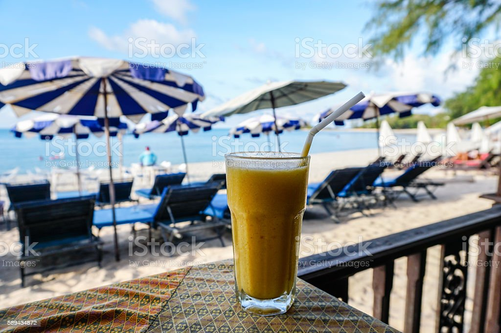 Glass of mango shake with sea view stock photo