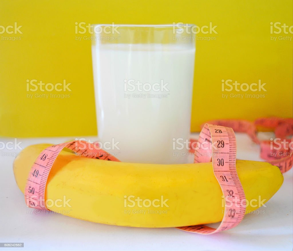 Glass of milk, a banana and a tape measure stock photo