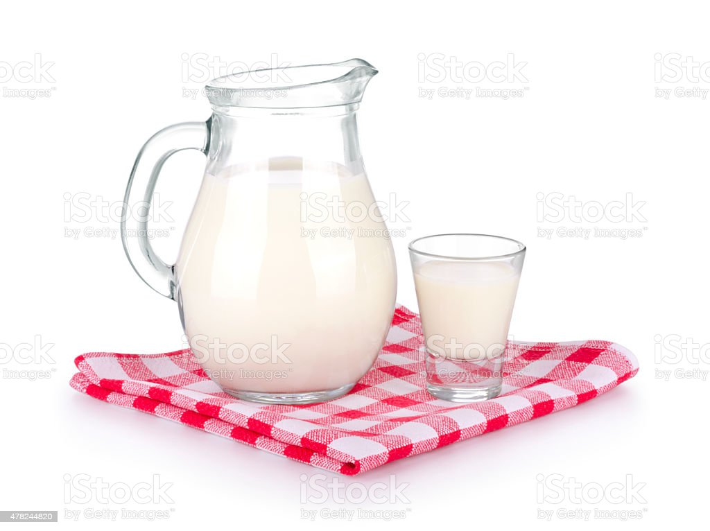 Glass of milk and a milk jug. stock photo