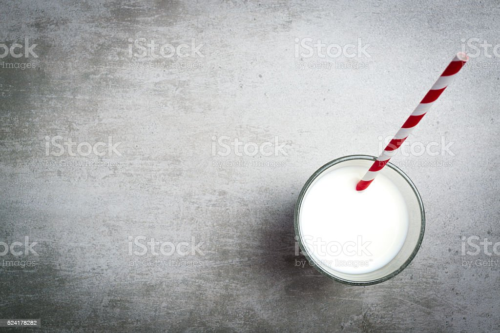 Glass of milk and a red and white drinking straw stock photo