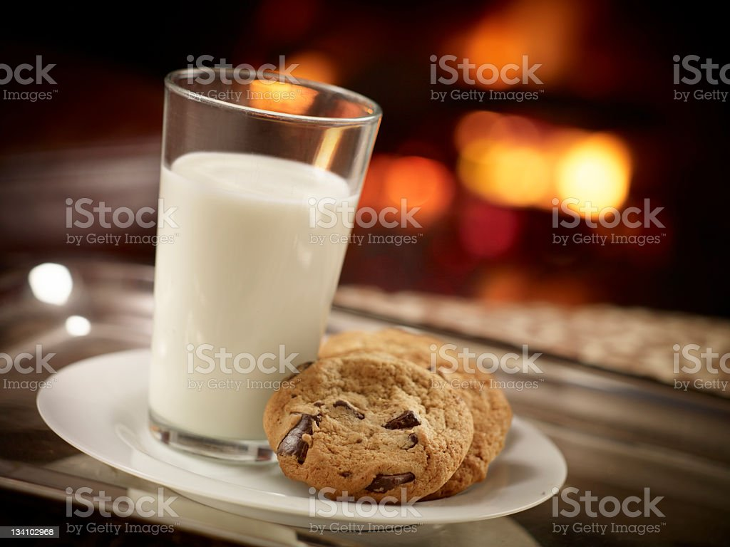 Glass of milk and plate of chocolate chip cookies stock photo