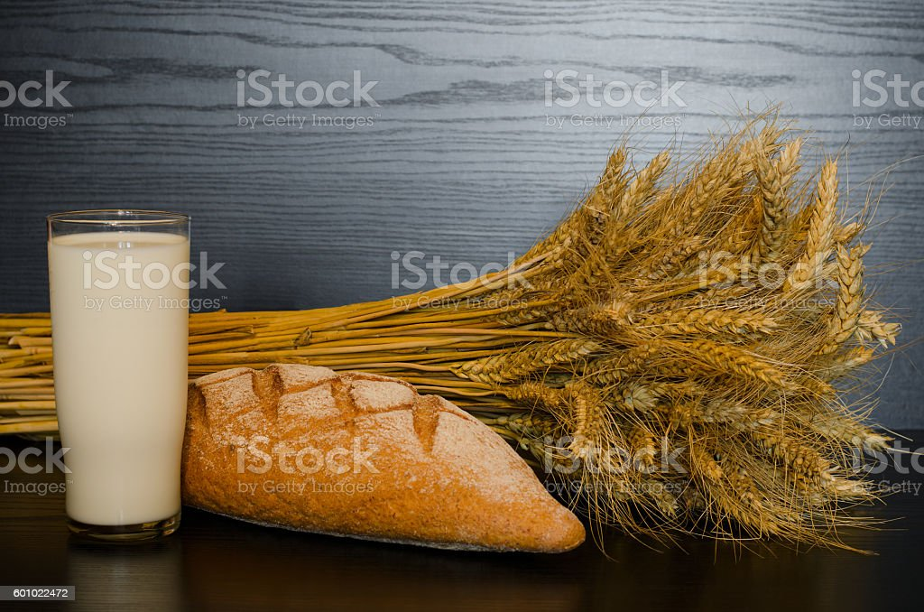 Glass of milk, bread and a sheaf on a dark background stock photo